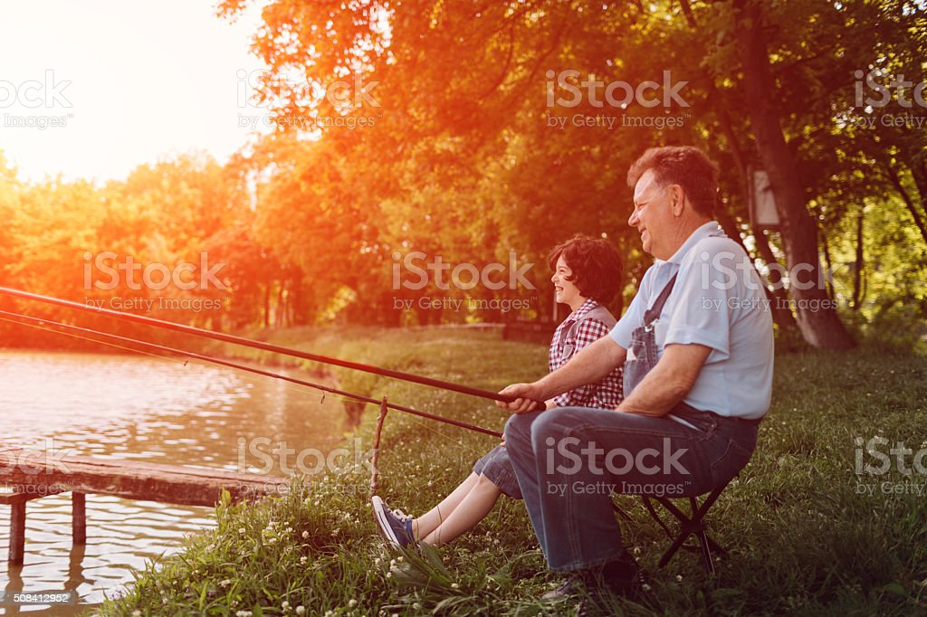 Grandpa and grandson fishing together stock photo