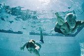 Grandpa and Grandson swimming underwater in summer