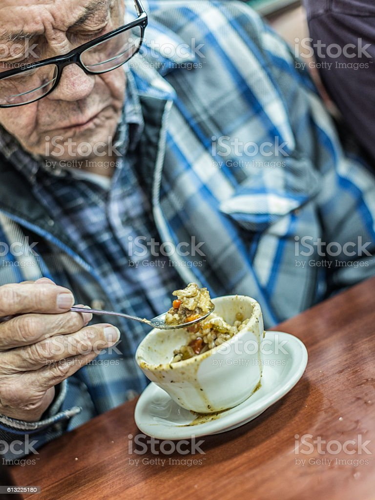 Grandpa Eating Cup of Lunch Soup and Crackers With Spoon stock photo