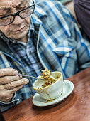 Grandpa Eating Cup of Lunch Soup and Crackers With Spoon