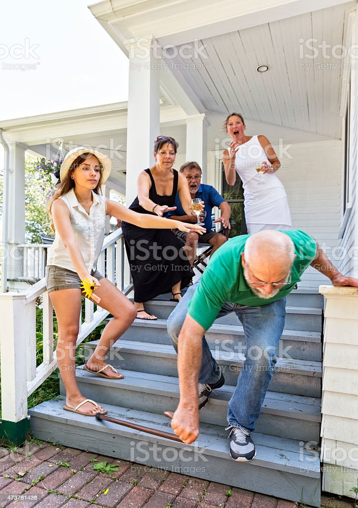 Grandpa Falls Down Steps While Friends and Family Watch stock photo