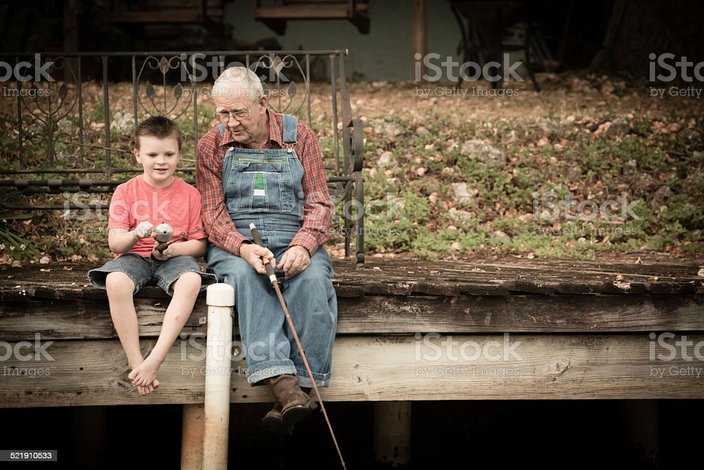 Grandpa Fishing With His Great Grandson on Wood Dock stock photo