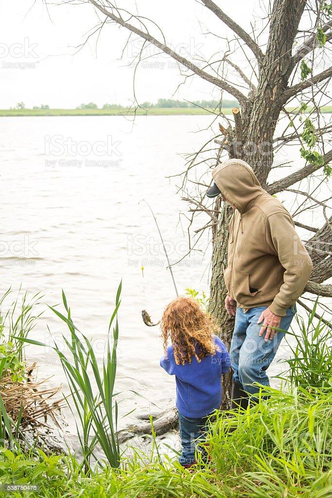 Grandpa & Granddaughter Fishing From Shore stock photo