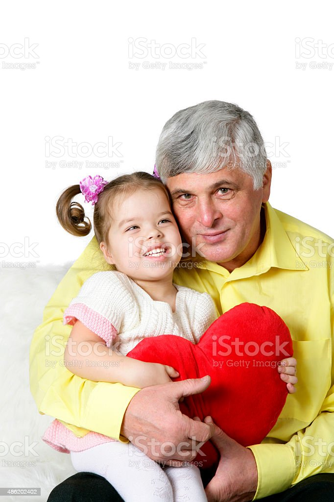 Grandpa hugging his lovely granddaughter with a red heart stock photo
