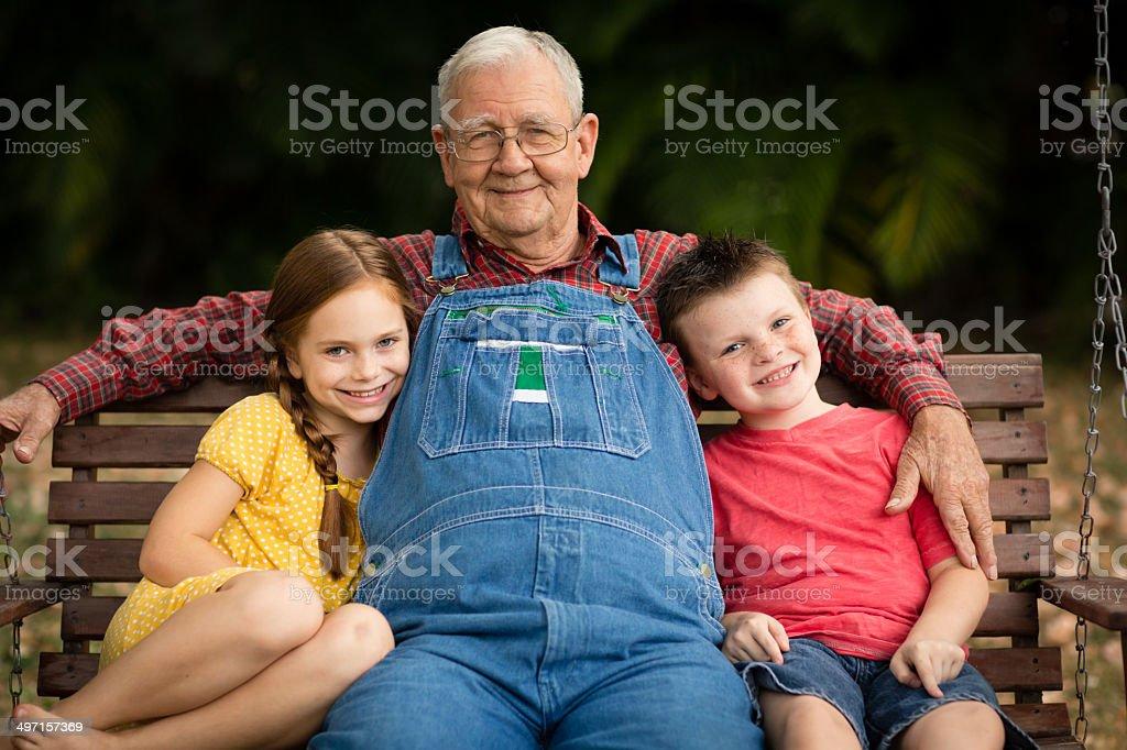 Grandpa Sitting on Porch Swing With His Great Grandchildren stock photo