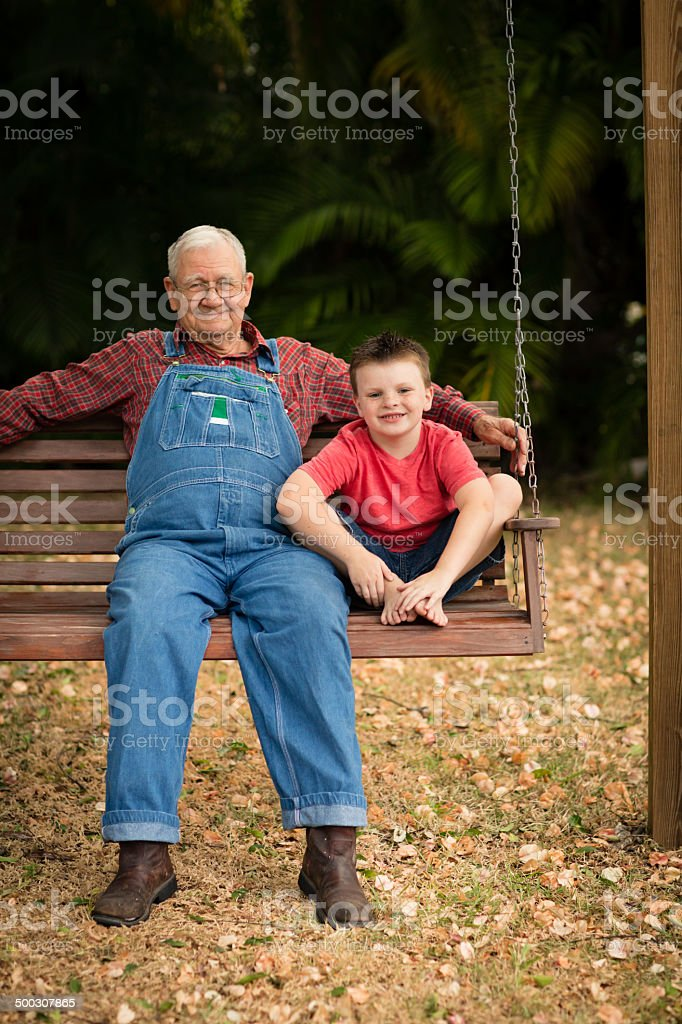 Grandpa Sitting on Porch Swing With His Great Grandson stock photo