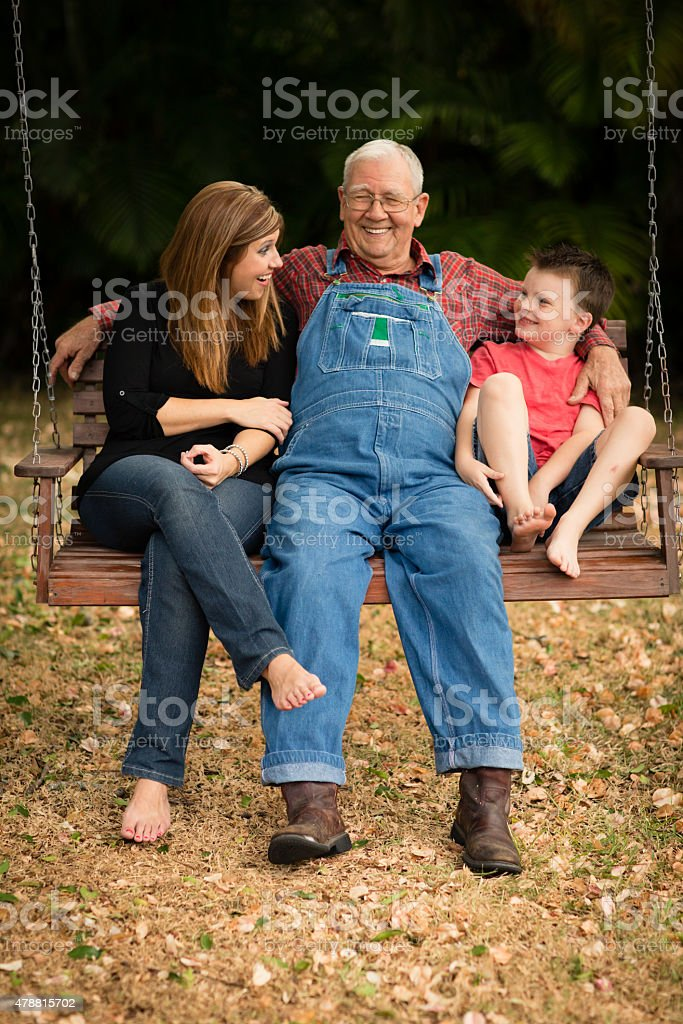 Grandpa Swinging With His Granddaughter and Great Grandson stock photo