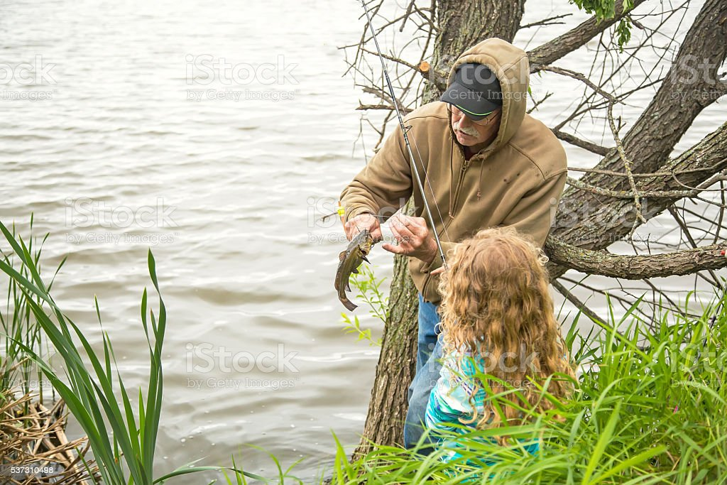 Grandpa Taking Fish Off Hook for Granddaughter Fishing stock photo