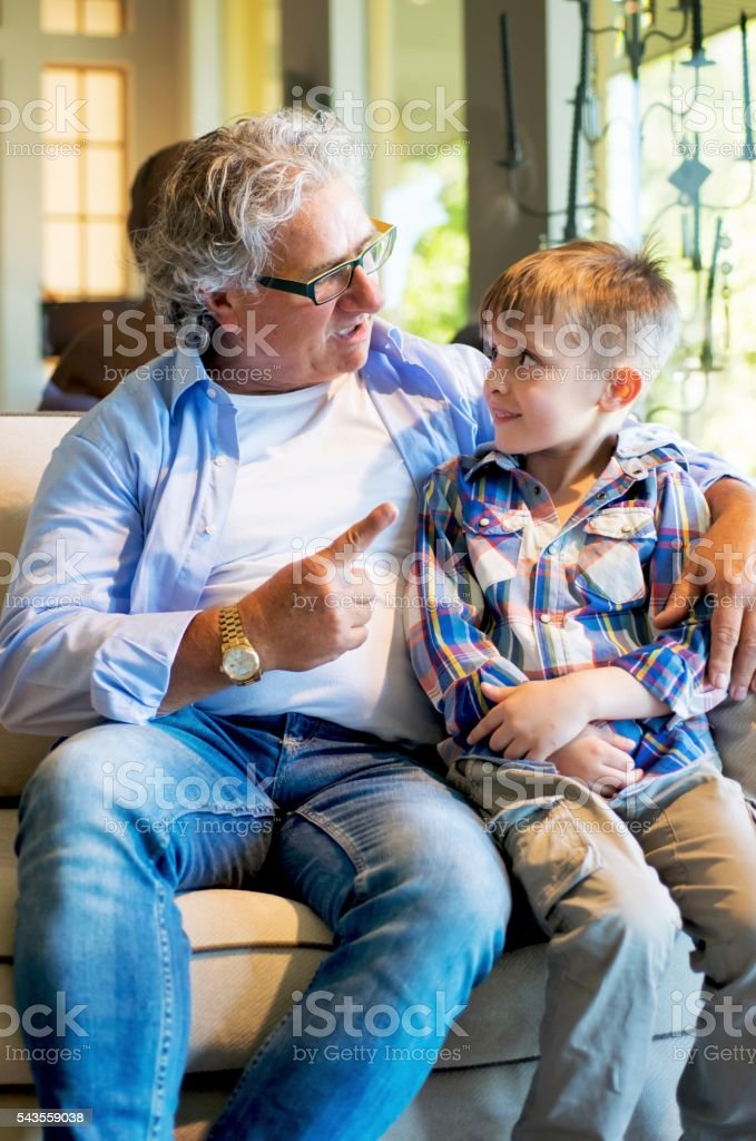 Grandpa Telling a Story at his Grandson stock photo