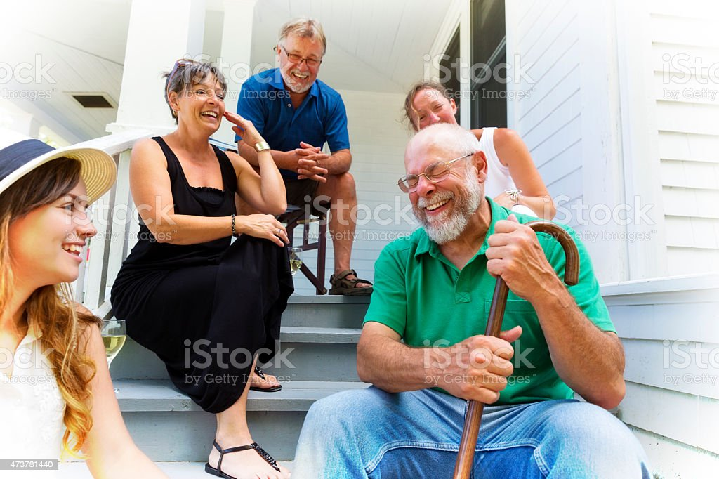 Grandpa Tells Funny Story to Friends and Family stock photo