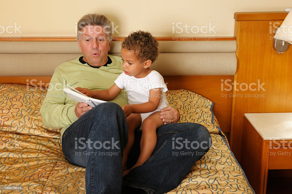 Grandparent/ Father Enjoying A Bedtime Story with Toddler royalty-free stock photo