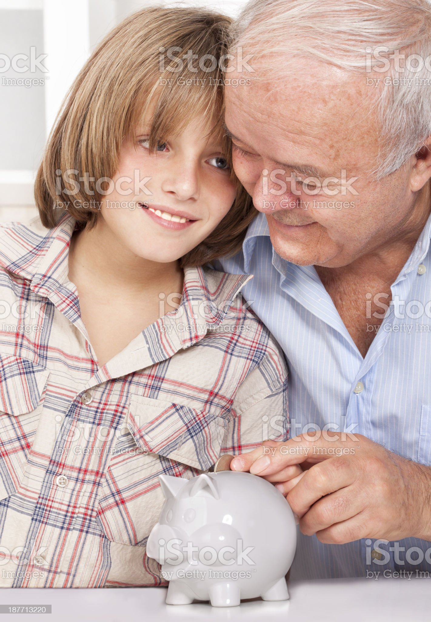 Grandparent teaching grandson to save money in a piggy bank royalty-free stock photo