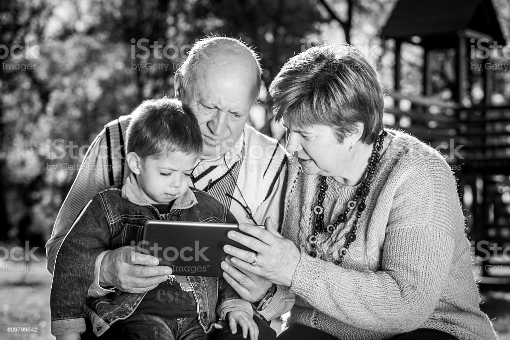 grandparents and grandchild using tablet on a bench stock photo
