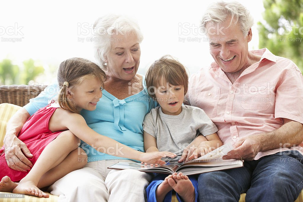 Grandparents And Grandchildren Reading Book On Garden Seat royalty-free stock photo