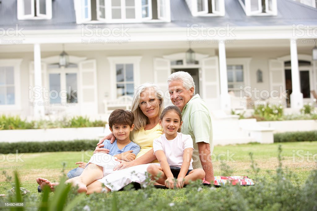Grandparents And Grandchildren Relaxing On Lawn Outside House royalty-free stock photo