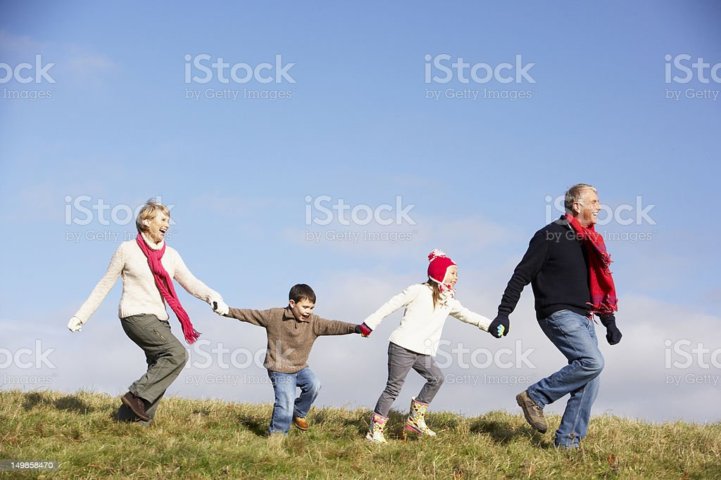 Grandparents And Grandchildren Running In The Park royalty-free stock photo