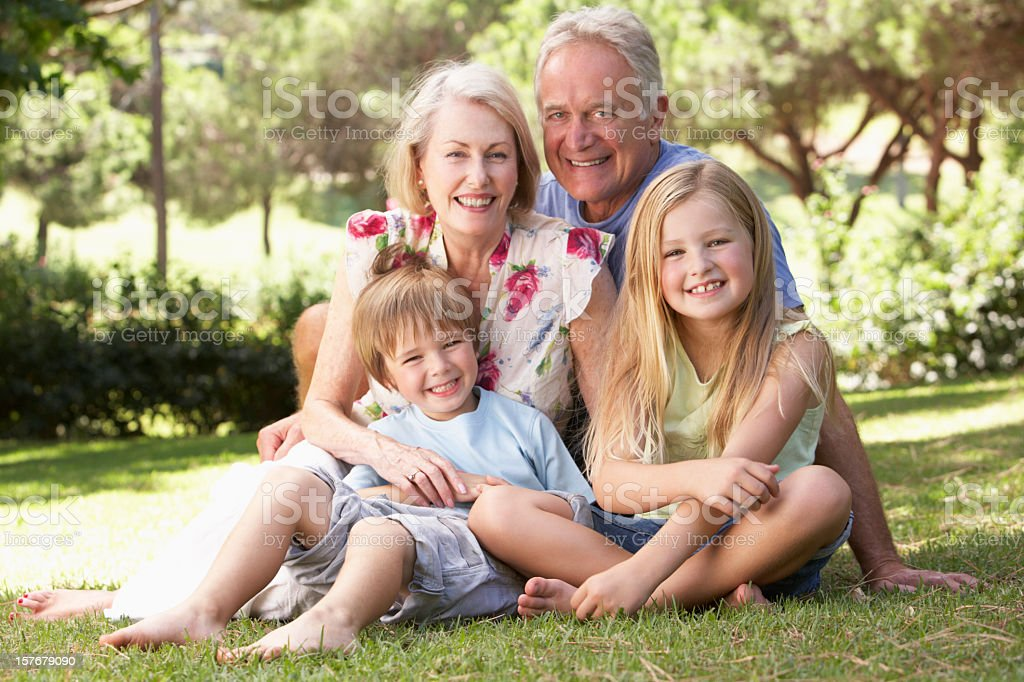 Grandparents And Grandchildren Sitting In Park royalty-free stock photo