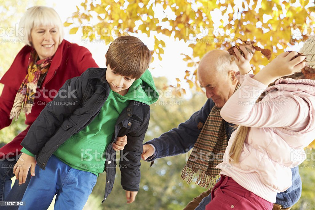 Grandparents And Grandchildren With Leaves In Autumn Garden royalty-free stock photo