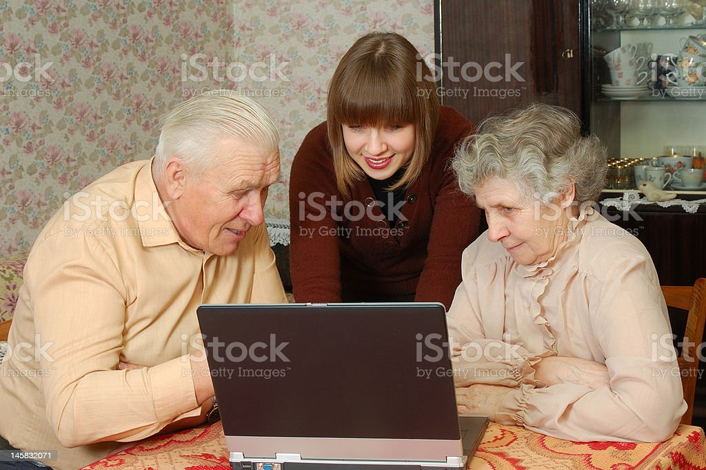 grandparents and granddaughter looking to the laptop royalty-free stock photo