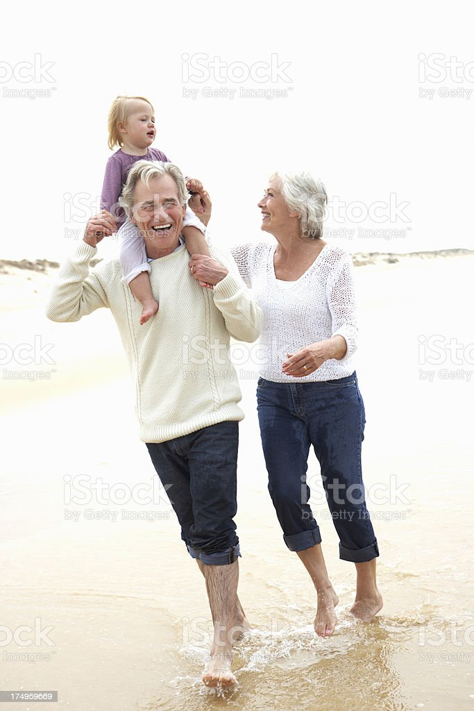 Grandparents And Granddaughter Walking Along Beach Together stock photo