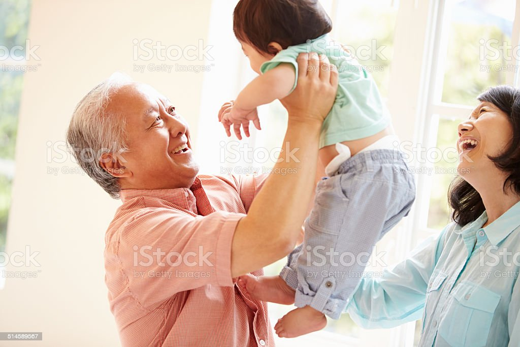 Grandparents And Grandson Playing Game Indoors Together stock photo