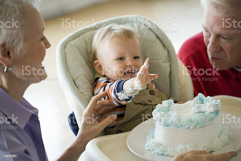 Grandparents and messy baby with cake stock photo