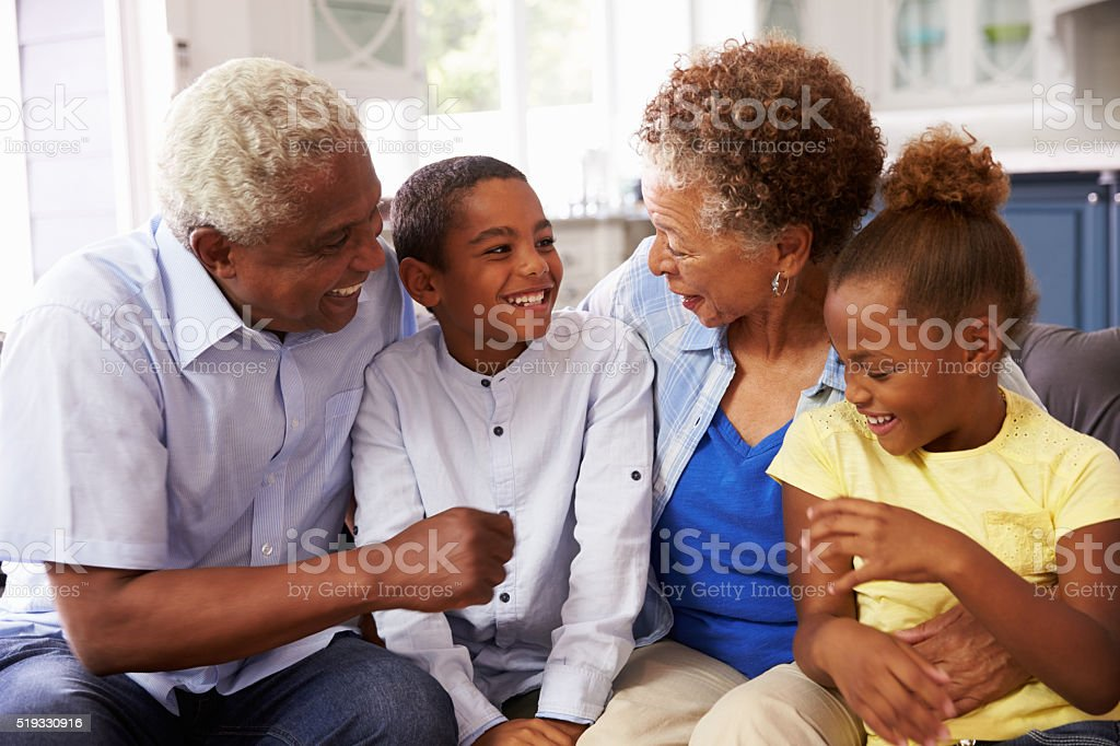 Grandparents and their young grandchildren relaxing at home stock photo
