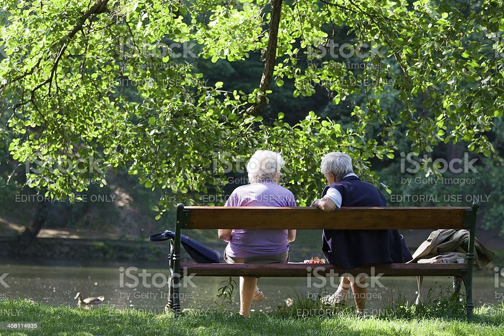 Grandparents are talking on the bench in spring park royalty-free stock photo