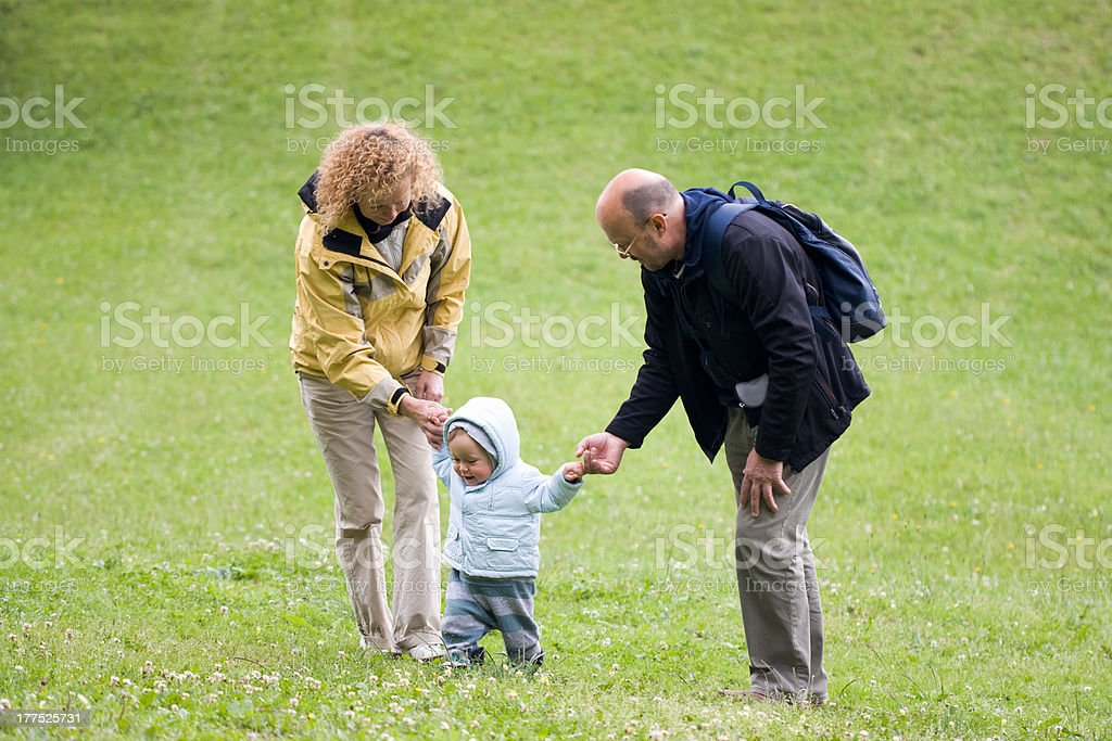 Grandparents are teaching walking their grandson royalty-free stock photo