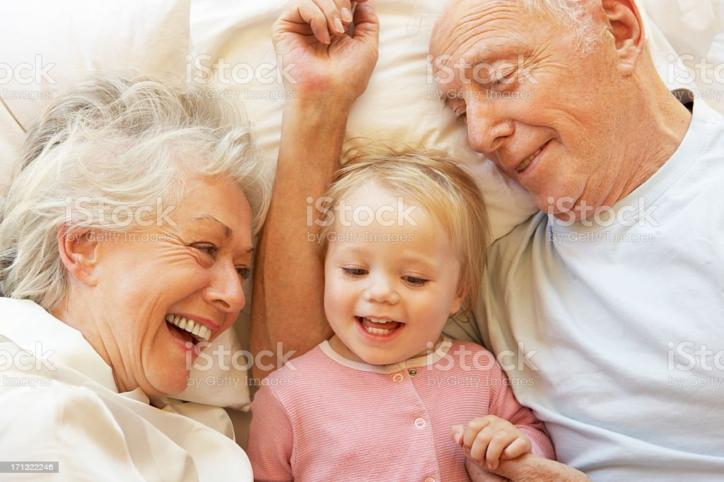 Grandparents Cuddling Granddaughter In Bed stock photo