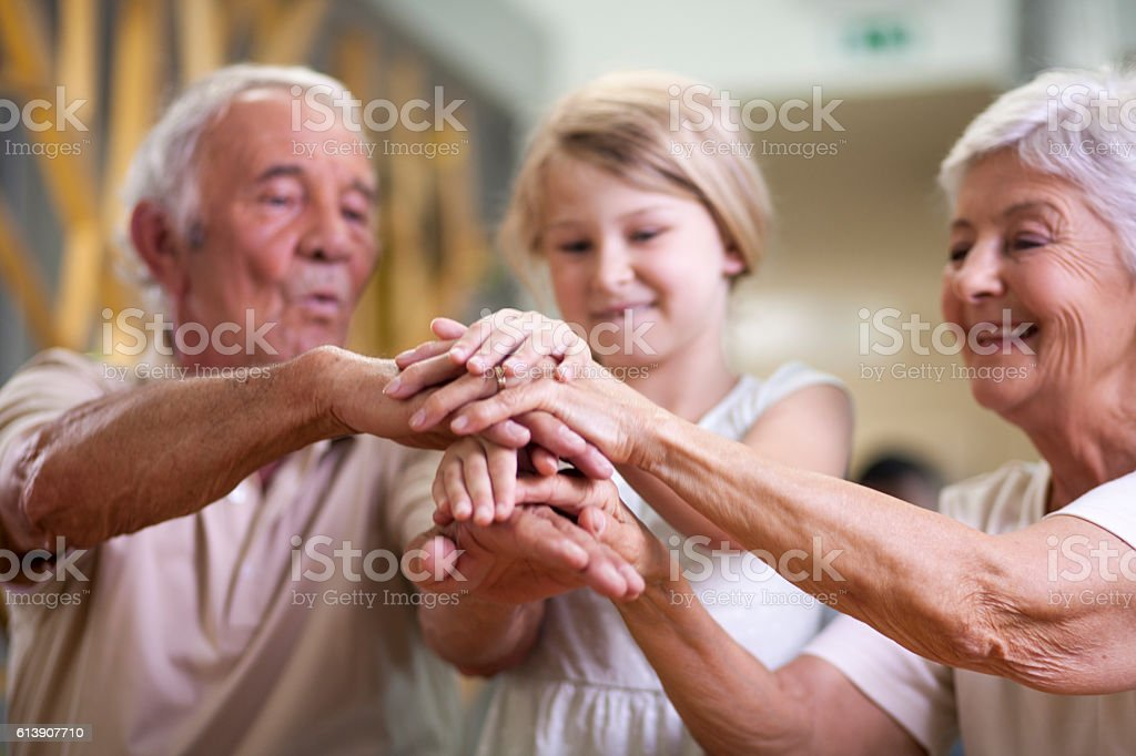 Grandparents, granddaughter and a hand game stock photo