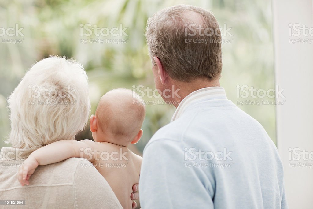 Grandparents holding baby and looking out window royalty-free stock photo