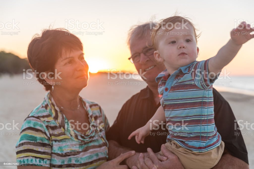 Grandparents Holding Baby Boy on Tropical Beach at Sunset stock photo