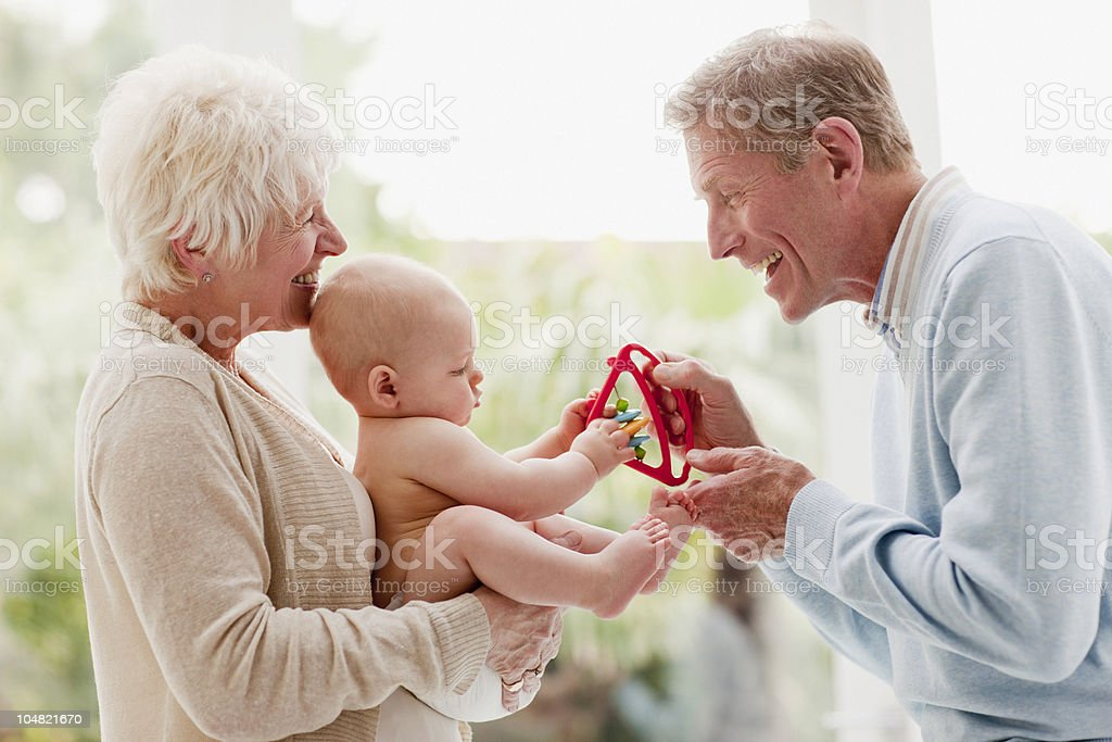 Grandparents holding baby with toy royalty-free stock photo
