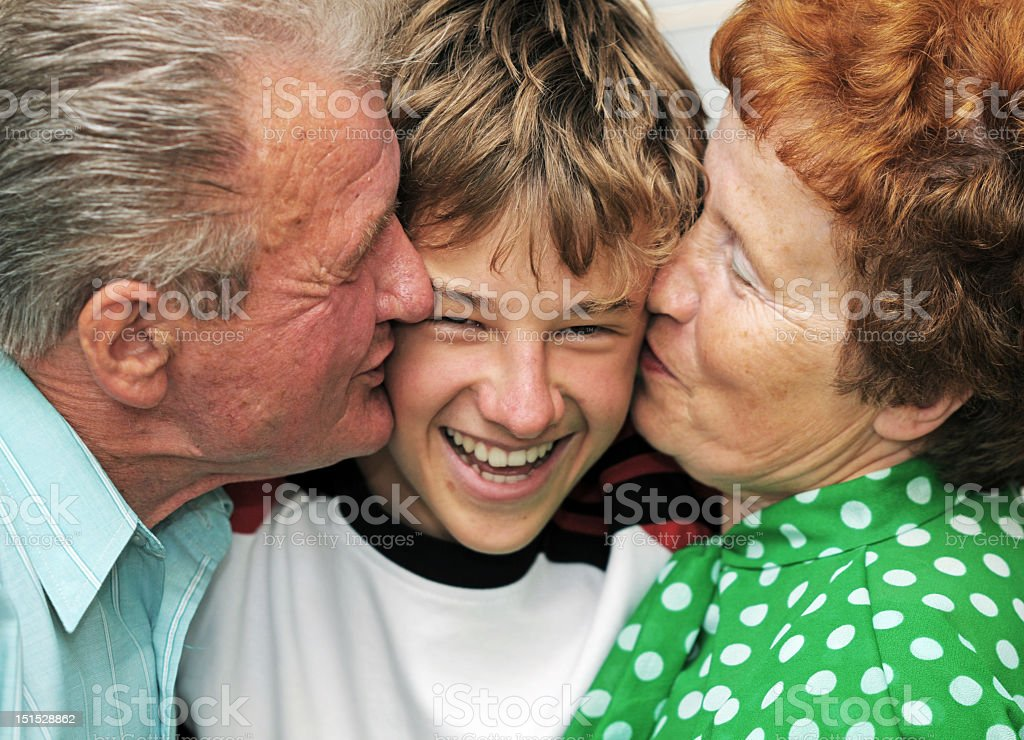Grandparents kissing their grandson on the cheek royalty-free stock photo