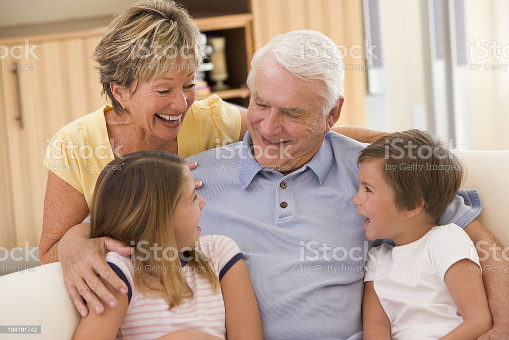 Grandparents laughing with grandchildren at home royalty-free stock photo