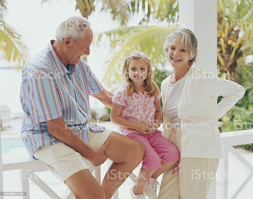 Grandparents on balcony with granddaughter (3-5) smiling royalty-free stock photo