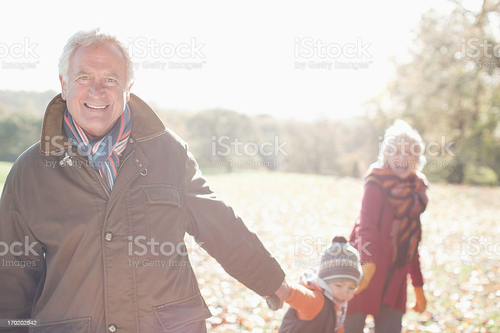 Grandparents playing in park with grandson stock photo