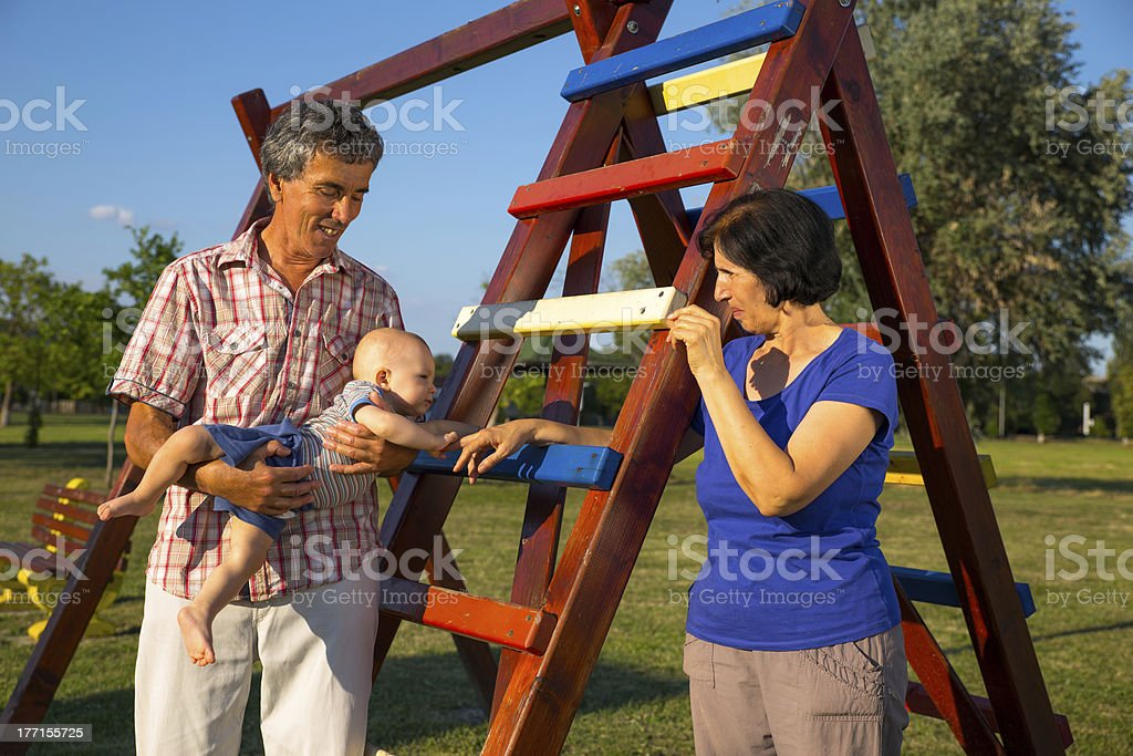 Grandparents Playing With Grandchildren In Playground royalty-free stock photo