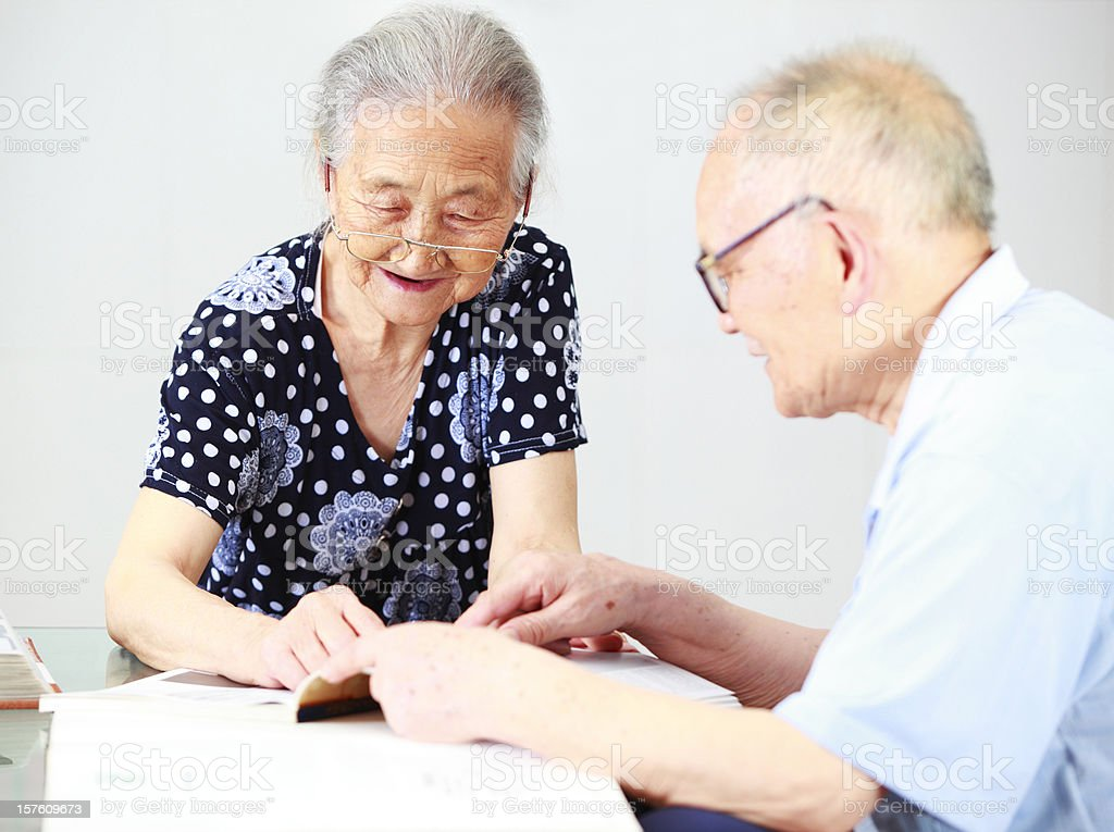 grandparents reading book together royalty-free stock photo