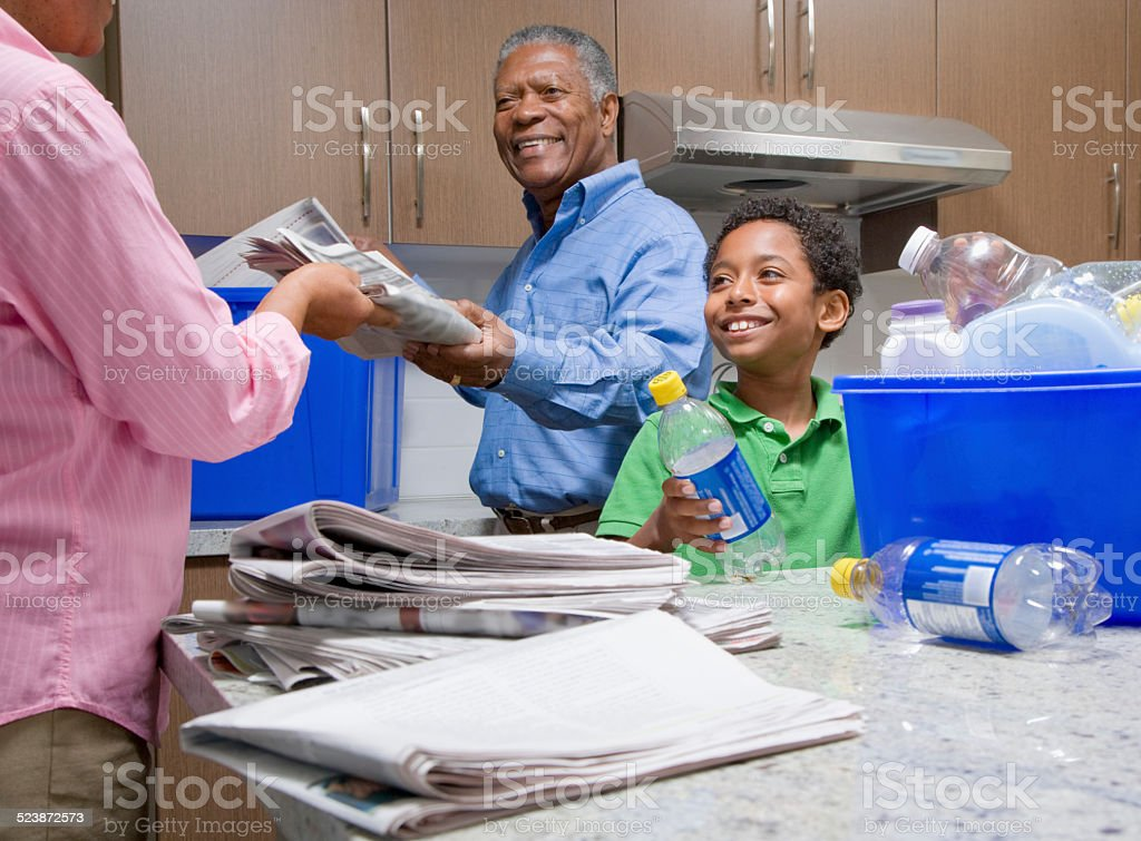 Grandparents Recycling With Grandson in Kitchen stock photo