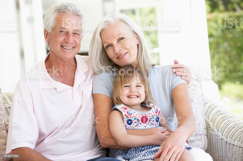 Grandparents Relaxing On Seat With Granddaughter royalty-free stock photo