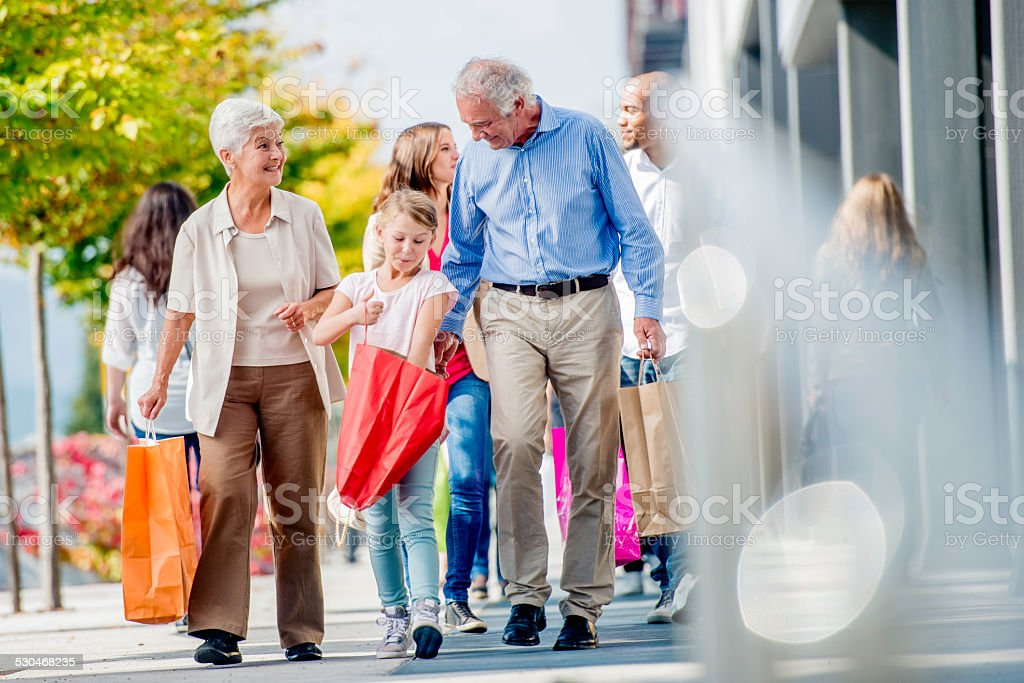 Grandparents Shopping with Their Granddaughter stock photo