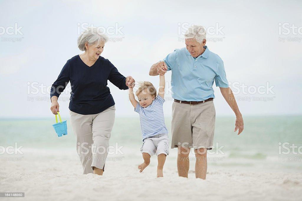 Grandparents Swinging Little Boy At Beach royalty-free stock photo