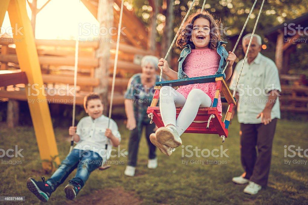 Grandparents swinging their grandchildren. stock photo