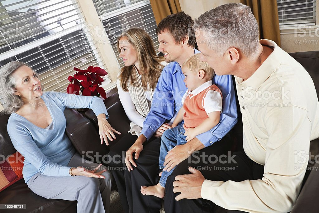 Grandparents Talking to Children's Family in Living Room stock photo