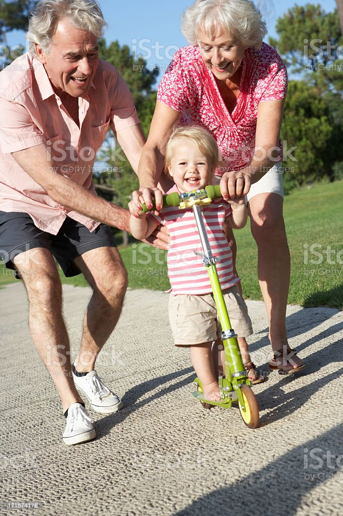 Grandparents Teaching Granddaughter To Ride Scooter In Park royalty-free stock photo