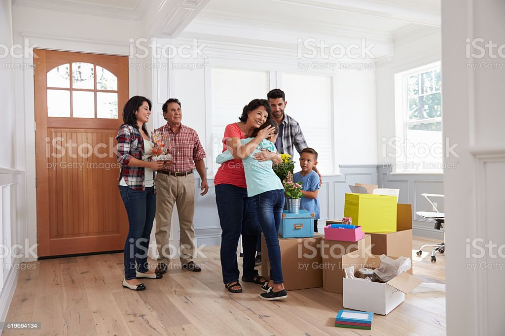 Grandparents Visiting Hispanic Family In New Home stock photo