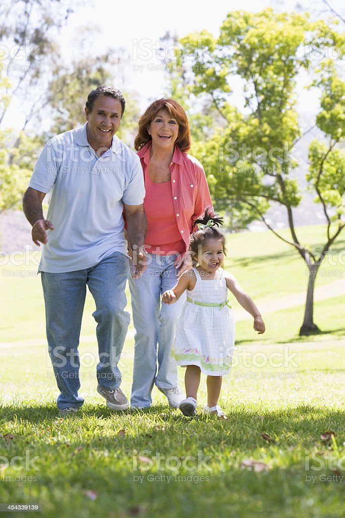 Grandparents walking in the park with their granddaughter royalty-free stock photo
