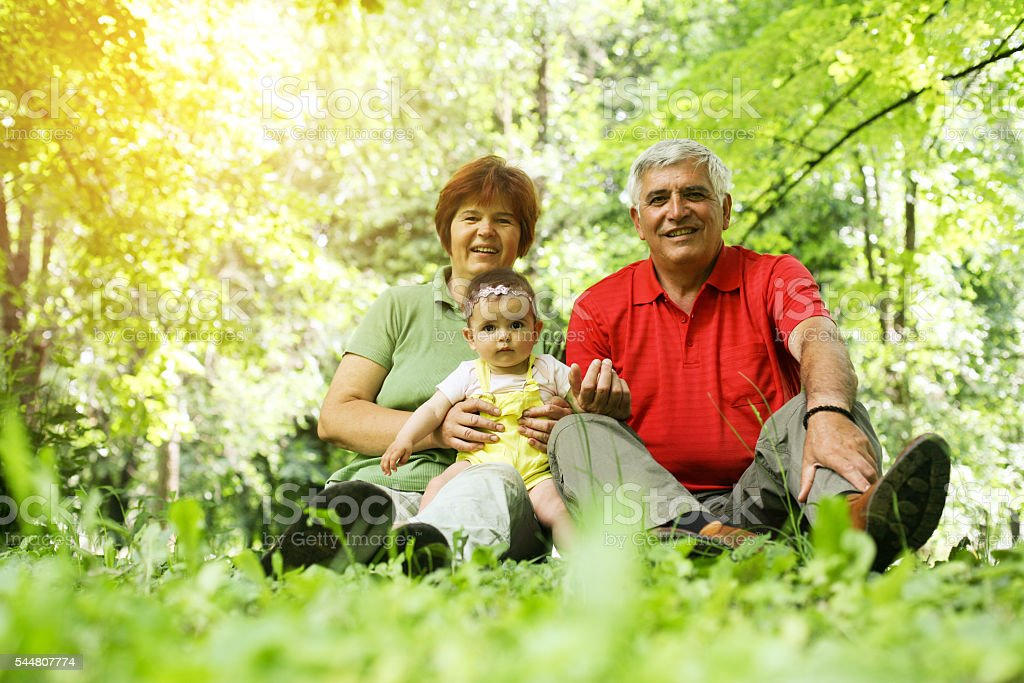 Grandparents with baby girl in the park. stock photo